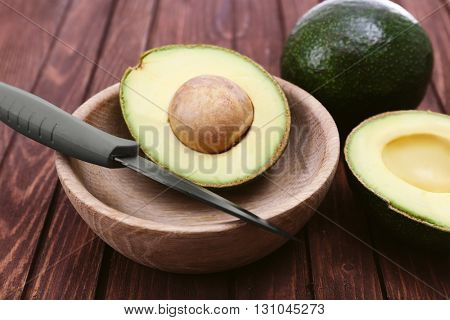 Fresh avocado in bowl on wooden background