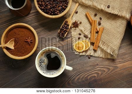 Coffee with beans and spices on wooden table, top view