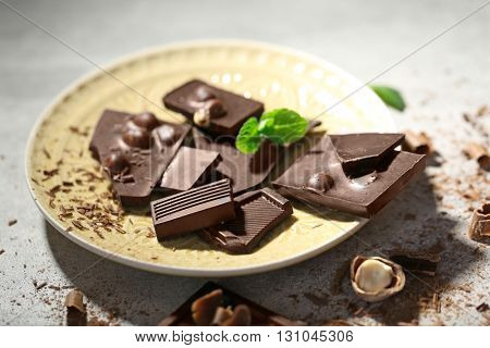 Broken black chocolate with hazelnuts and fresh mint on a plate