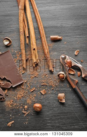 Pieces of chocolate with hazelnuts, cracker and cinnamon on black wooden background