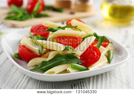 Boiled penne pasta with tomatoes, French bean and arugula on white plate