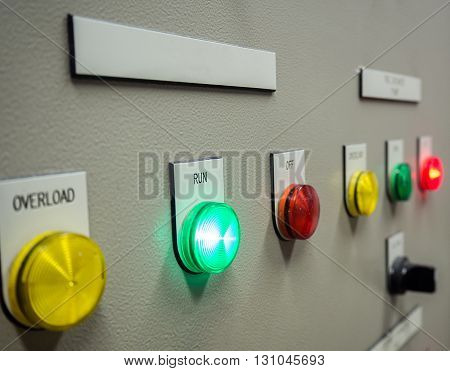 Status indicator light and selective switch of Auto-Manual on electrical control panel with blank name tag.Selective focus on running status light.