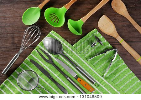 Set of kitchen tools with green napkin on wooden table