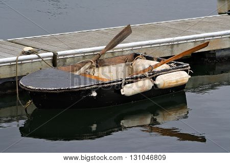Small Black row boat tied to dock