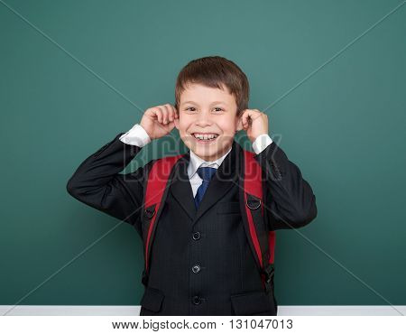 school boy make faces in black suit on green chalkboard background with red backpack, education concept