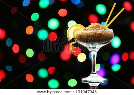 Margarita glass with brown granulated sugar on dark bokeh background