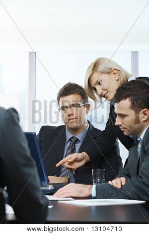 Empresarios mirando el ordenador portátil, hablando en la mesa de la reunión en la oficina,