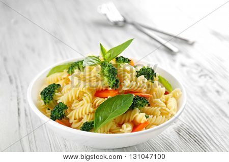 Boiled fusilli pasta with carrot, broccoli and basil on white plate