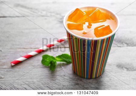 Orange drink in bright paper cup on wooden background
