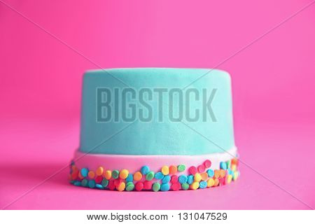 Birthday cake with sprinkles on pink background.