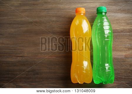 Bottles with soft drinks on the wooden table, top view