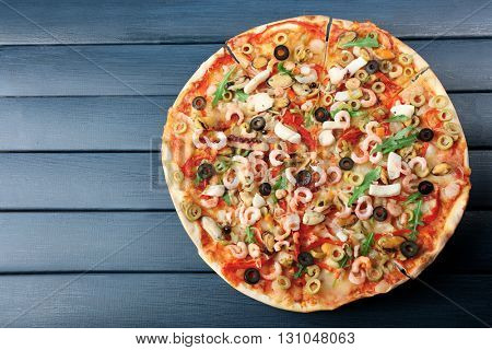 Pizza with seafood, red pepper and olives on blue wooden table