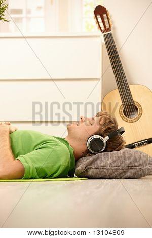 Goodlooking Mann liegend am Boden des Wohnzimmers, hören von Musik über Kopfhörer, lächelnd mit geschlossenen e