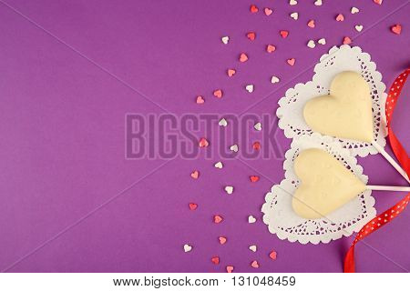 White heart lollipops with red ribbon on purple background