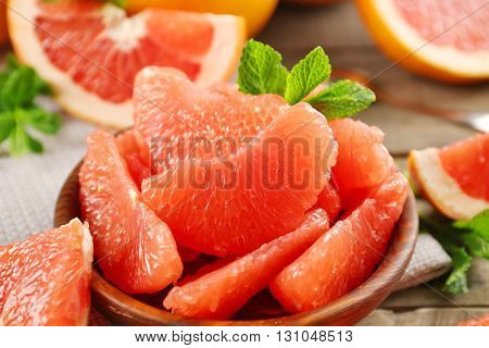 Juicy grapefruit pieces with fresh mint in a bowl, close up