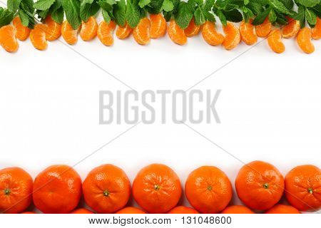 Colorful orange tangerines with slices and mint sprigs  on a white background with copy space, top view