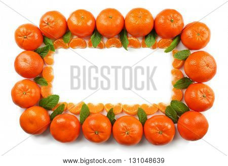 Colorful orange tangerines with mint sprigs and slices on a white background, top view