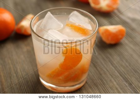 One fresh delicious tangerine cocktail with ice and mandarins on the wooden table, close up