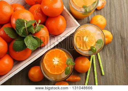 Delicious tangerine cocktails with ice, mint, served on a wooden table, top view
