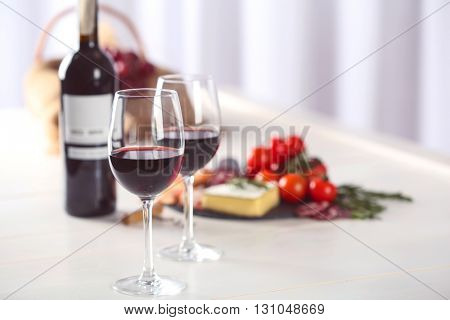 Glasses of red wine with food on blurred background