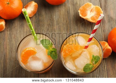 Two fresh delicious tangerine cocktails with ice, mint, straws and mandarins on the wooden table, top view