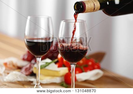 Pouring of red wine into glass and food on wooden table closeup