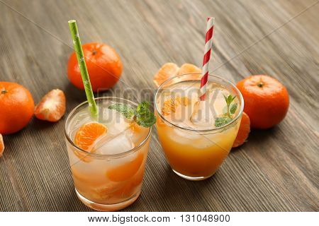 Two fresh delicious tangerine cocktails with ice, mint, straws and mandarins on the wooden table, close up