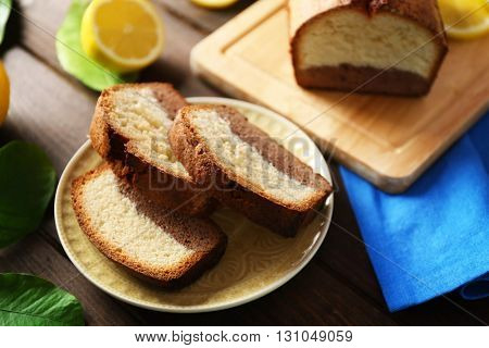 Delicious sweet cake bread with lemons on wooden table closeup