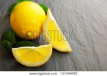 Slices of fresh lemon with green leaves on table closeup
