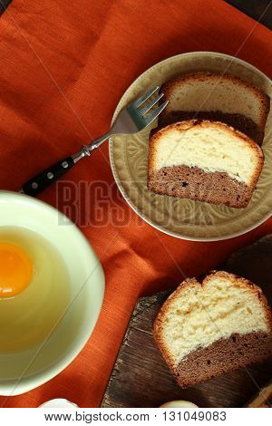 Delicious sweet cake bread with lemons on orange napkin, top view
