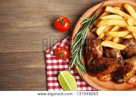 Baked chicken wings with French fries on brown plate