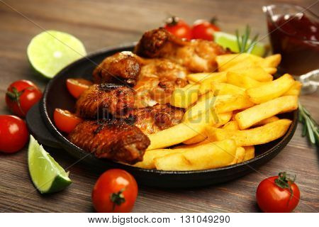 Baked chicken wings with French fries on wooden table