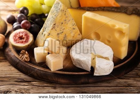 Delicious various cheese on old wooden table