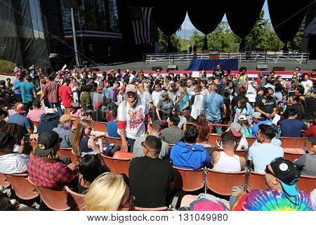 IRVINE, CALIFORNIA - May 22: Fans Smile, Wave Signs as they wait in the stadium of the Irvine Meadows Amphitheater for Bernie Sanders at a Rally in Irvine, California on May 22, 2016