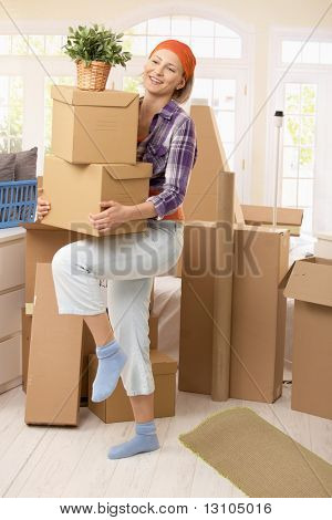 Smiling woman carrying boxes at moving house.