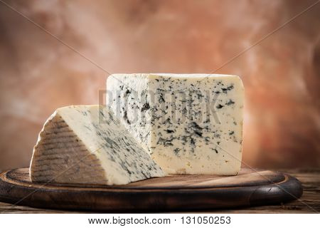 Blue cheese on wooden background, close-up.