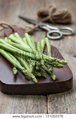 fresh asparagus on a cutting board scissors thread on the old wooden background