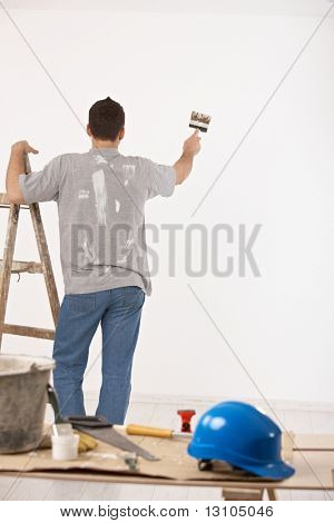 Guy painting wall white with paint brush, standing beside ladder.