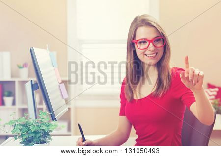 Young Woman Pointing To Something In Her Home Office