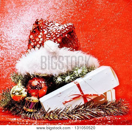 christmas decoration , red background with snow for post card greetings, toy design on tree macro xmas gifts under santas hat shining