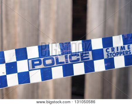 Melbourne, Australia -May 16, 2016: Blue and white Police tape cordoning off broken fence area at a residential house like a crime scene