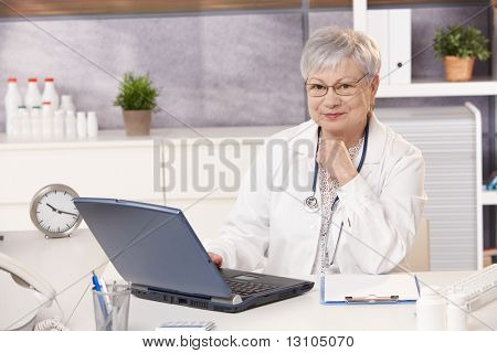Portrait of senior doctor in office, sitting at desk, looking at camera, smiling.