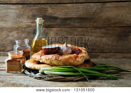 Fresh fried bread with other products on wooden background