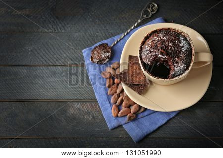 Chocolate fondant cake in cup on wooden background