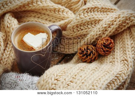 Cup of coffee with marshmallow on wooden table
