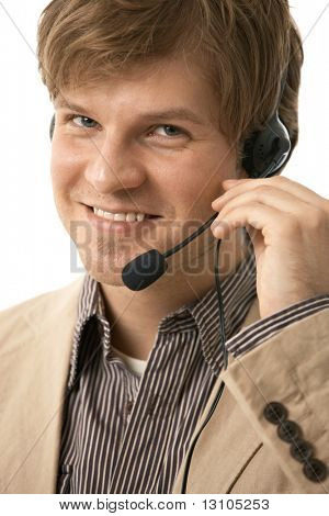 Closeup portrait of happy young man talking on headset, holding microphone. Isolated on white.
