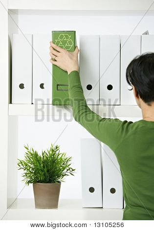 Female office worker choosing green folder with recycling symbol.
