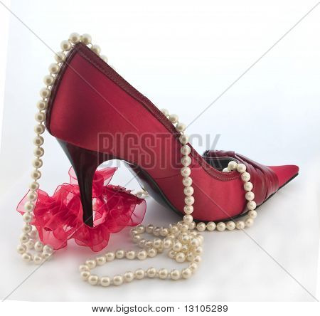 Red Shoe With Red Garter For Stocking And Pearls On White Background