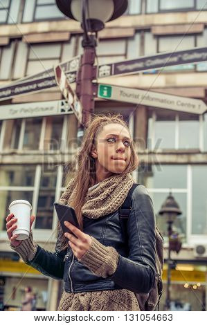 Beautiful female tourist standing in front of city road signs while holding a mobile phone and coffee