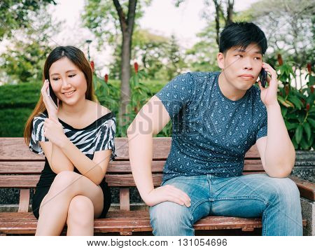 Asian Couple Talking On The Phone With Different Emotions - Indicating One Side Is Not Happy